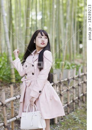 竹林の背景の前で目線外しのポーズをとる淡いピンクのトレンチコートの若い女性 18289213