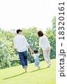 公園を手をつないで歩く3人家族の後ろ姿 18320161