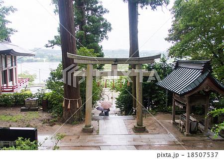 雨の日の神社。鳥居と傘をさす人の後ろ姿 18507537
