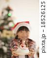 クリスマスツリーの前でケーキを差し出す女の子 18526125