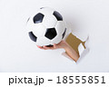 Hand holding soccer ball through the paper hole 18555851