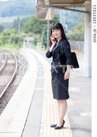 駅のホームで通勤電車を待つOL 18635821