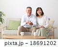 仲良くテレビを見るシニア夫婦 18691202