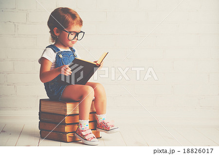 child little girl with glasses reading a books 18826017