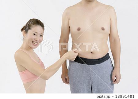 太った男性のお腹の肉をつまむスリムな若い女性の写真素材