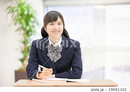 机に座って勉強している制服姿の女子高生のポーズ 19091102