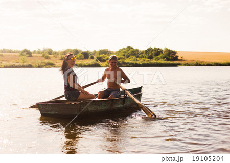 Happy romantic couple rowing a boat on lake. 19105204