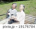 ベンチでコーヒーを飲む60代夫婦 19176784