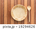 Empty wooden bowl and soup spoon on wooden table 19294626