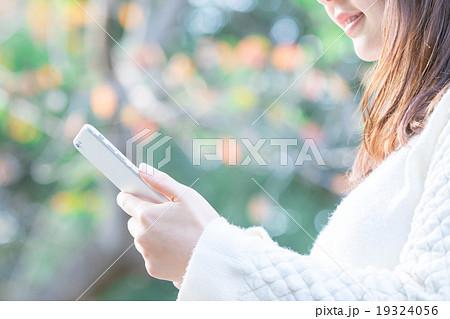 屋外で携帯電話で調べ物をする女性 検索 携帯をいじる スマートフォン スマホ 手元 パーツ 19324056