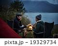 焚き火の前で乾杯をするカップル 19329734