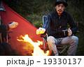 焚き火で暖まる男性 19330137