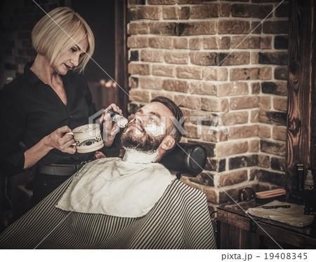 client during beard shaving in barber shop 19408345 pixta. Black Bedroom Furniture Sets. Home Design Ideas