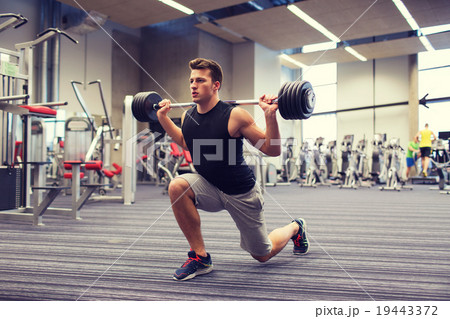 young man flexing muscles with barbell in gym 19443372