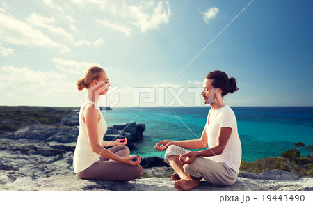 happy couple meditating in lotus pose on beachの写真素材