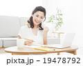 パソコンを見ながらメモする若い女性 19478792
