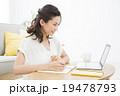 パソコンを見ながらメモする若い女性 19478793