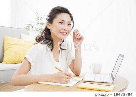 パソコンを見ながらメモする若い女性 19478794