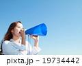 青空をバックにメガホンで応援するロングヘアの綺麗な若い女性 19734442