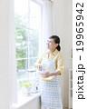 窓辺に立つエプロン姿の女性 19965942