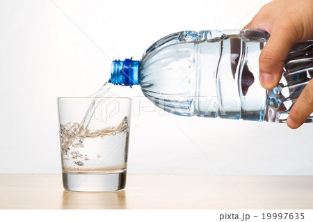 Hand pouring refreshing mineral water from bottleの写真素材 [19997635] - PIXTA