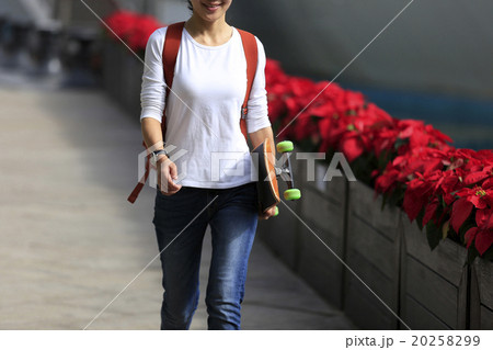 young woman skateboarder walking with skateboard 20258299