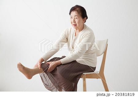 シニア女性 椅子に座って足をのばす(リハビリ体操) 20381819