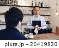カフェでオーナーと話す男性 20419826