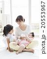 赤ちゃんにミルクをあげるお母さんと女の子 20553967
