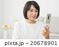 リビングで携帯電話を使う40代女性 20678901