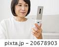 リビングで携帯電話を使う40代女性 20678903