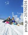 雪の丘でソリ遊びをする4人家族 20700256