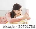 ソファでスマホを操作する若い女性 20701738