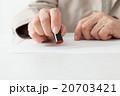 シニア女性 書類に印鑑を押す 20703421
