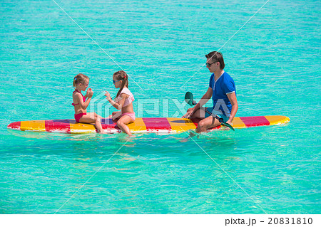 Little girls and young dad on surfboard during 20831810