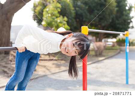 鉄棒で遊ぶ小学生の女の子の写真...
