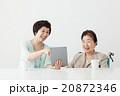 タブレットを一緒に見ている親子 車椅子の高齢者シニア女性とミドル女性 20872346