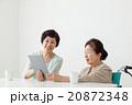 タブレットを一緒に見ている親子 車椅子の高齢者シニア女性とミドル女性 20872348