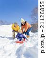 雪の公園でソリ遊びをする3人家族 21126855
