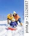 雪の公園でソリ遊びをする3人家族 21126857