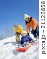 雪の公園でソリ遊びをする3人家族 21126858