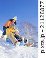 雪の公園でソリ遊びをする3人家族 21126877