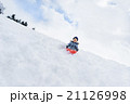 雪の公園でソリ遊びをする男の子 21126998