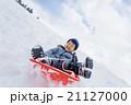 雪の公園でソリ遊びをする男の子 21127000
