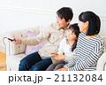 リモコンを持ちテレビを見る3人家族 家族団らん 父親 母親 娘 コピースペース 仲のいい家族 21132084