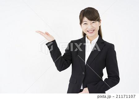 ビジネススーツを着た魅力的な笑顔が素敵なモデル女性「正面」ご案内こちらです,どうぞ,業務案内,会社説明,会社案内,企業説明会,商品説明21171107