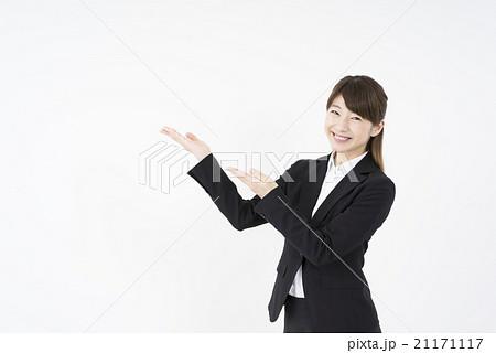 ビジネススーツを着た魅力的な笑顔が素敵な女性「斜め」両手でご案内,こちらです,どうぞ,会社概要と商品説明に誘導する21171117