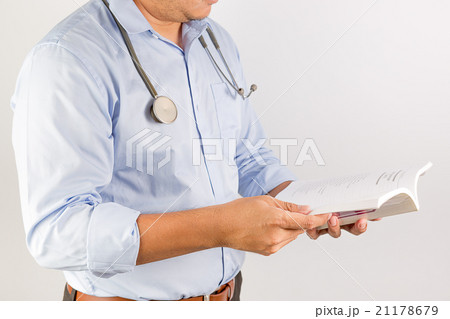Male doctor holding his stethoscope, reading 21178679