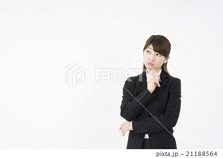 ビジネススーツを着て困って考え事をする若い女性先輩「正面」新人教育成どうしよう,悩み,不安,心配,残業,ブラック企業,人事異動,転勤,クレーム処理,生理痛,体調不良,トラブルに巻き込まれ,クレーム処理,恋愛相談,サービス残業,21188564