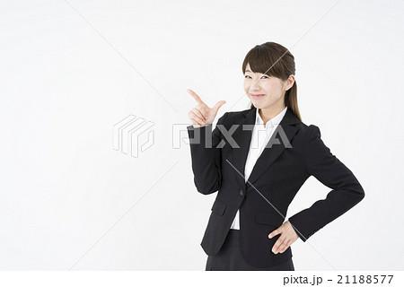 ビジネススーツを着て腰に手を当てゆびを指す女性「正面」指差S字チャンスです。これです。こちらです21188577